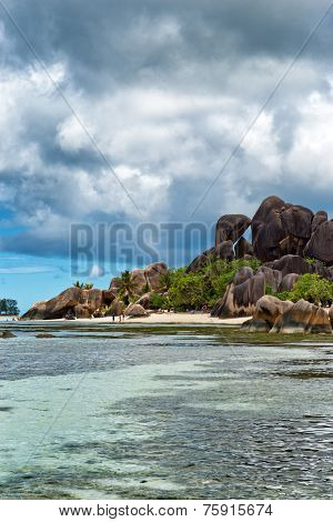 Enchanting Tourist Destination with Clear Blue Green Water Lagoon and Large Rock Forms on the Landscape in Seychelles Island. Captured with Stormy Sky Above.