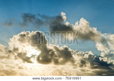Bank of clouds with a glowing sun backlighting the edges in a blue summer sky for a spectacular celestial background