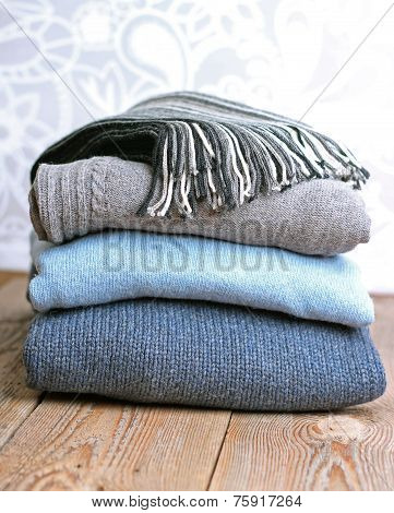 Pile Of Warm Wool Clothing On A Wooden Table