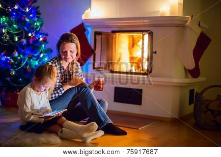 Family of mother and daughter sitting by a fireplace in their home on winter