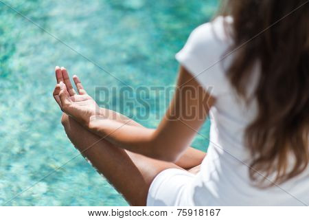 Over the shoulder view from behind of a long haired young woman meditating above a calm sea with focus to her hand resting on her knee in the lotus position