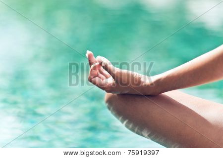Close up view of the graceful hand gesture of a woman meditating overlooking a pool with tranquil blue sunlit water