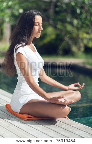 Close up Side View of Young Slender Asian Indian Woman Meditating at the Poolside