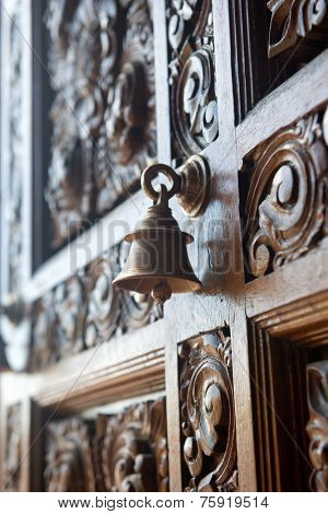 Old brass bell on an ornately carved door embellished with a swirling handcrafted pattern viewed at an oblique angle with incoming light