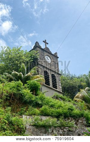 Clocktower of St Pauls Cathedral, Victoria, Mahe rising above lush green tropical vegetation under a blue sky
