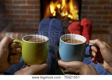 Couple With Hot Drink Relaxing By Fire
