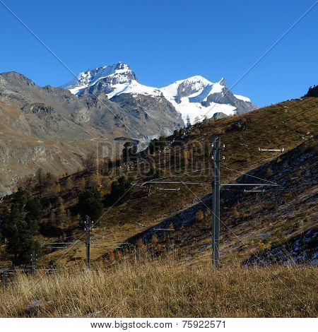 Snow Capped Mountains And Power Poles Of The Train To The Gornergrat