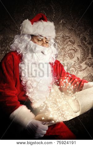 Christmas concept with Santa Claus in costume holding wish list. Dark pattern as background