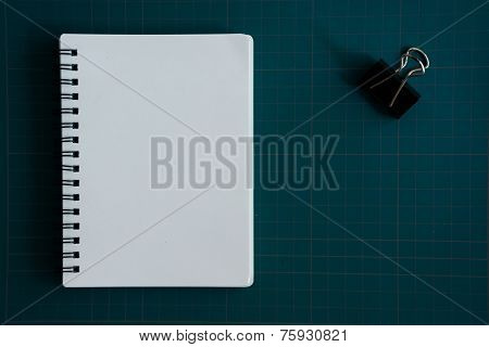 Notebook and paper clip on cutting board