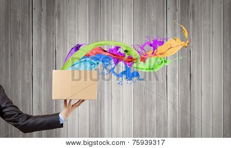 Close up of hand holding carton box with colorful splashes