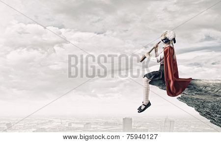 Cute supergirl of school age with looking in spyglass