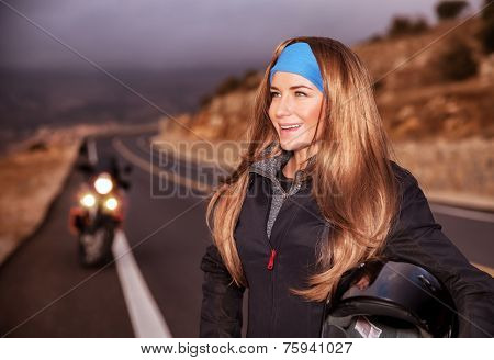 Portrait of nice happy young biker on the road, beautiful girl enjoying extreme sport, bike ride adventures, active lifestyle
