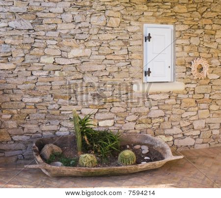 Flowerbed With A Cactus In A Tub Near The Wall Of Rough Stone