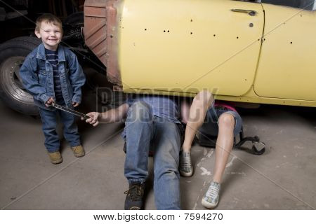Son Handing Father A Tool