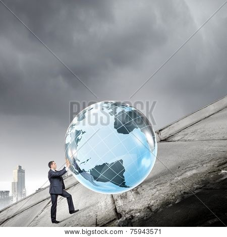 Young businessman rolling Earth planet up th hill