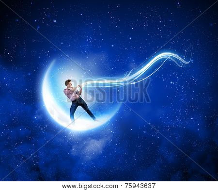 Young man in casual catching moon with rope