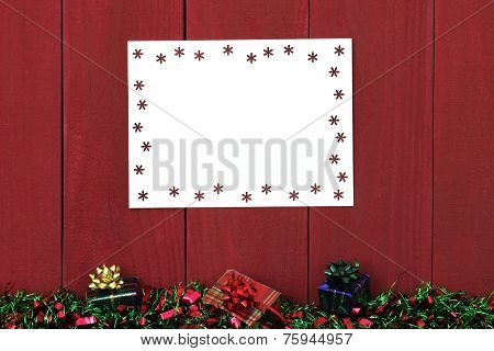 Snowflake sign with Christmas garland border and presents hanging on antique red wooden background