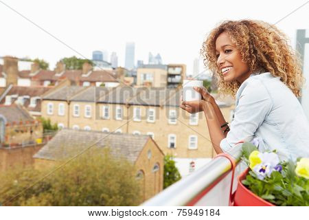 Woman Relaxing Outdoors On Rooftop Garden