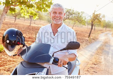Mature Man Riding Motor Scooter Along Country Road