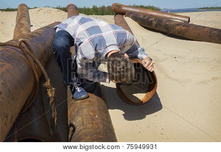Very curious young man looks into  pipe