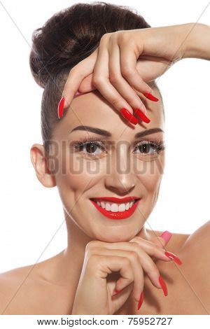 Portrait of young beautiful smiling girl with long red nails and lipstick over white background