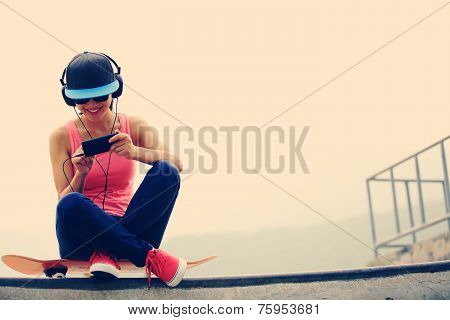 woman skateboarder listening music from cellphone mp3 player on skatepark