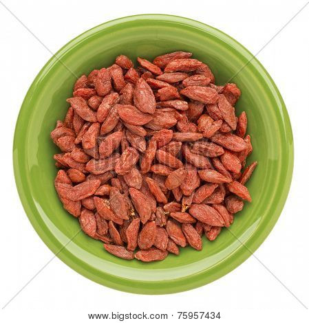 dried goji berries on an isolated green ceramic bowl - superfood abstract