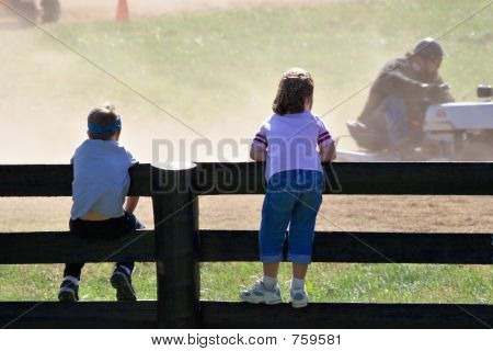 Boy and girl looking at small car race