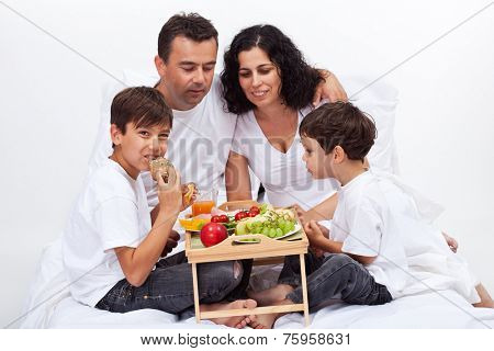 Healthy breakfast in bed - family eating fruits and fresh bakery products