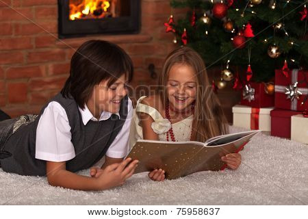 Kids reading a book - in front of the Christmas tree and a fireplace