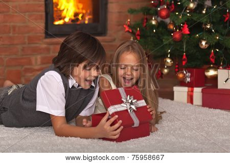 Kids opening their Christmas present - in front of the tree and fireplace