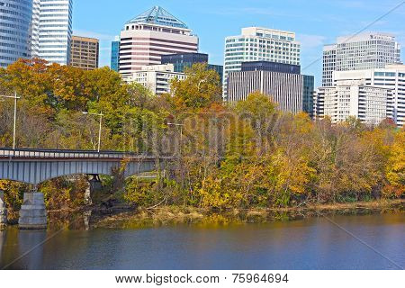 Modern building near Potomac River surrounded by trees with fall foliage.