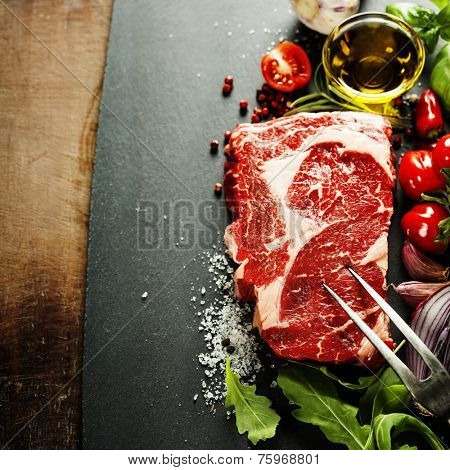 Raw beef steak with meat fork on a dark slate background