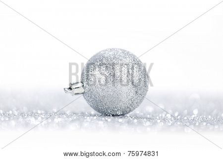 One chritmas ball on glitters isolated on white background