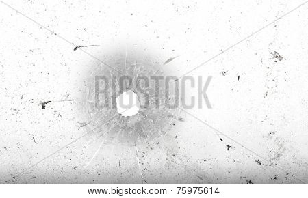 Bullet hole in glass on dirty grungy white background