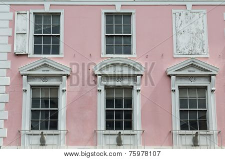 White Windows On Old Pink Government Building In Bahamas