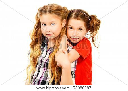 Two smiling girls embracing each other like best friends. Isolated over white.