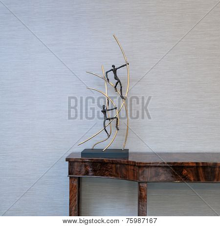 Sideboard In Front Of A Grey Wall And Art Objects