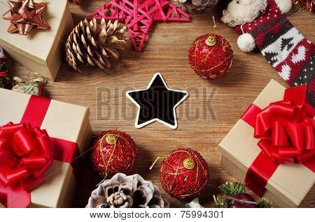 a pile of gifts and christmas ornaments, such as christmas balls and stars, on a rustic wooden table with a blank heart-shaped chalkboard in the center