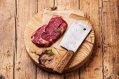 picture of ribeye steak  - Raw fresh meat Ribeye Steak and meat cleaver on wooden background - JPG