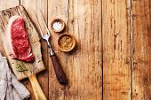 foto of meats  - Raw fresh meat Striploin steak and meat fork on wooden background - JPG