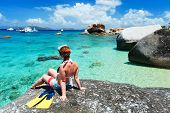 image of virginity  - Young woman with snorkeling equipment enjoying view of a tropical beach sitting on granite boulder at Virgin Gorda - JPG