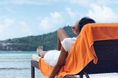 picture of beachfront  - Asian Indian Woman Relaxing on Beach Chair with Towel at the Beachfront - JPG