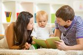 image of young baby  - Young parents mom and dad reading children book to baby son