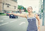 picture of hail  - Young beautiful woman dressed striped dress trying to hail a cab in the city - JPG