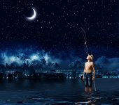stock photo of boys night out  - Young boy at night with fishing rod - JPG