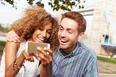 picture of two women taking cell phone  - Couple Taking Selfie By Tower Bridge In London - JPG