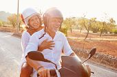 picture of scooter  - Mature Couple Riding Motor Scooter Along Country Road - JPG