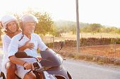 stock photo of scooter  - Mature Couple Riding Motor Scooter Along Country Road - JPG
