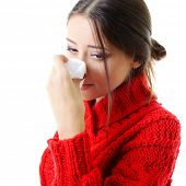picture of sneezing  - Portrait of a young woman sneezing in to tissue  - JPG